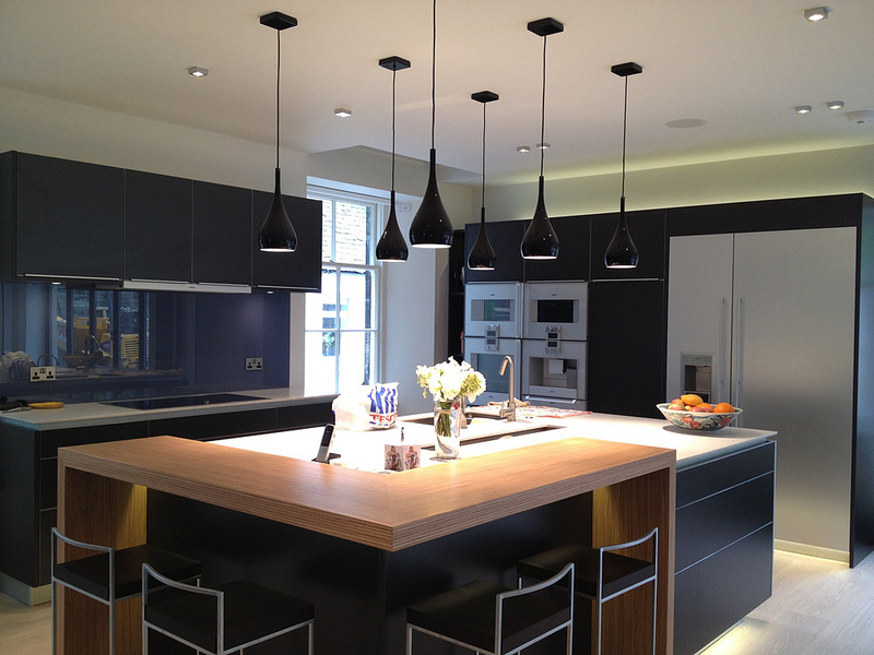 Image Of Dark Kitchen With Large Square Island And Stainless Steel  Appliances