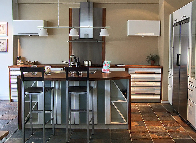 Silver Kitchen Cabinets With Stylish Island And Rust Colored Tile Flooring